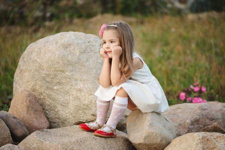 Kleines Mädchen auf dem großen Stein Standard-Bild - 80120415