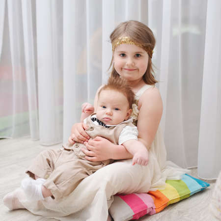 little girld holds her younger brother
