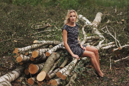 Beautiful girl in the felled forest Stock Photo