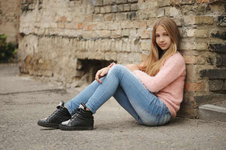 Beautiful young girl posing on the street Фото со стока