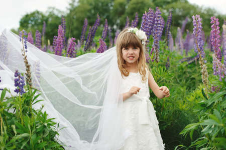 Little beautiful girl with bride dress Фото со стока