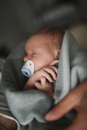父格子縞の生まれたばかりの赤ちゃんを保持 写真素材