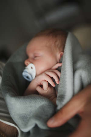 Father holding newborn baby in plaid Stock Photo