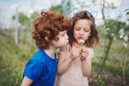 Little boy and girl in blooming garden Stock Photo