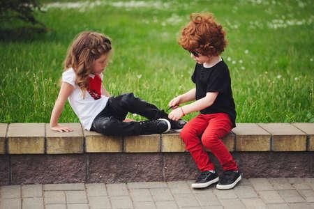 소년 도움이 어린 소녀 넥타이 신발 끈