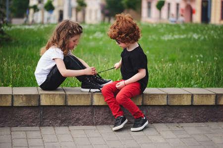 El muchacho ayuda a los lazos de la corbata de la niña Foto de archivo - 83623919