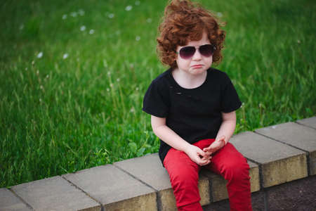 sad red haired boy in summer park Stock Photo - 83623942