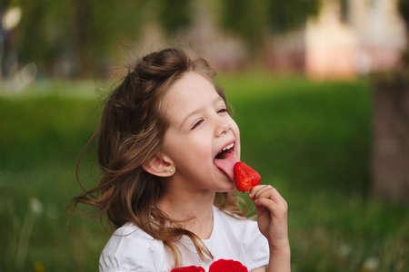 큰 육즙 딸기 먹는 아름다운 소녀