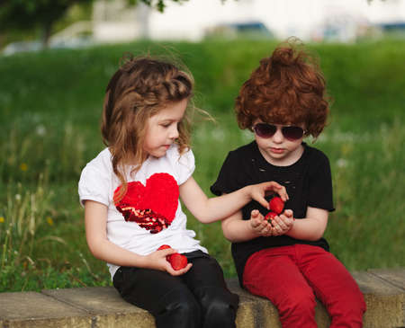 funny boy and girl sharing strawberry Standard-Bild