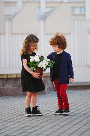 Little boy and girl with big lilac bouquet photo