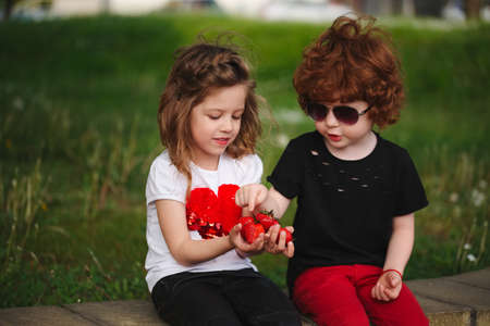 Funny boy and girl sharing strawberry photo