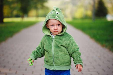 little unhappy boy with dinosaur costume Stock Photo - 83624686