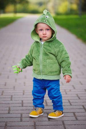 Little unhappy boy with dinosaur costume Stock Photo