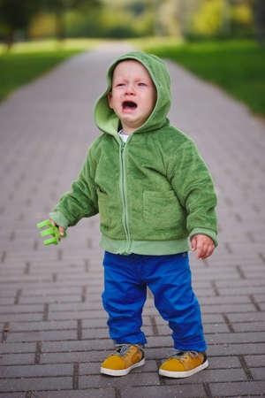 little unhappy boy with dinosaur costume