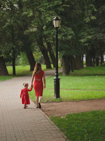 girl with mother walking in summer park