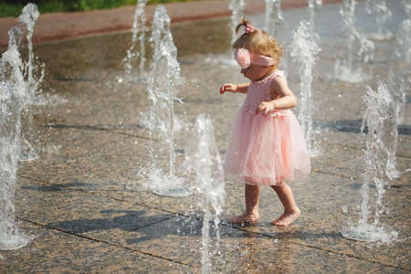 little girl plays with water in fountain