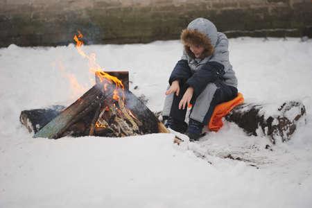 jongen zit bij vuur op straat