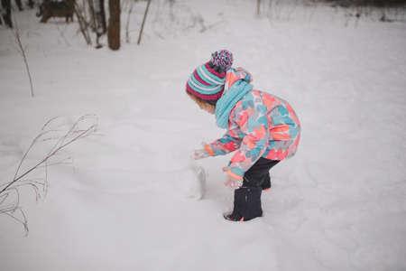 girl makes snowman in winter park Stock Photo