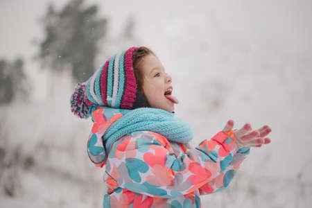 Bambina che cattura i fiocchi di neve nel parco invernale Archivio Fotografico - 88928152