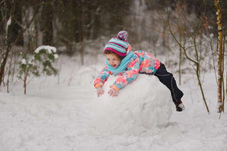 girl makes snowman in winter park Zdjęcie Seryjne