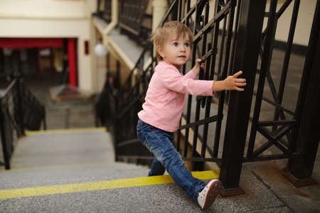 little cute girl climbs up on stairway
