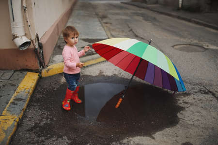 little girl plays in the puddle outdoors