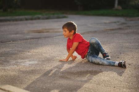 little boy lying on asphalt on the street