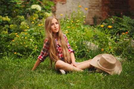 beautiful young girl with long hair sit on grass