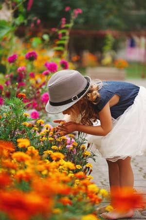 花の公園の小さな美しい女の子