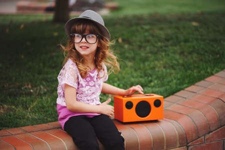 little hipster girl listens music on wireless retro looking spea Stock Photo