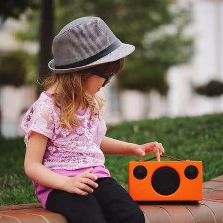 little beautiful hipster girl listens music on wireless retro looking speaker