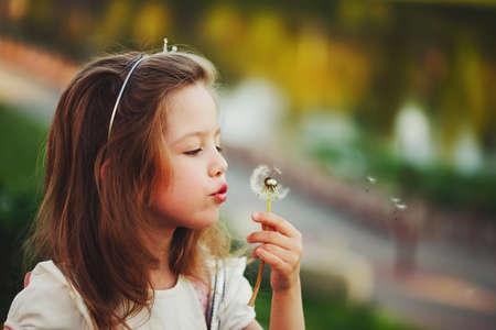 little girl with dandelion in park Banco de Imagens