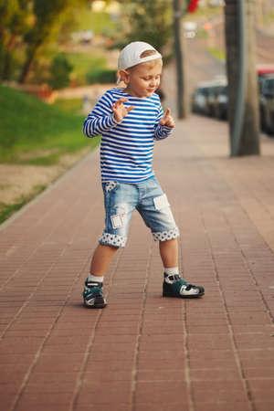 little boy dancing on the street