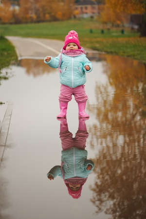 little girl with rubber boots in puddle Banque d'images - 105225312