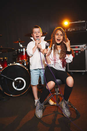 boy and girl singing in recording studio