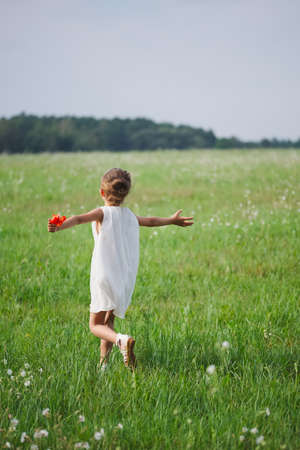 cute little girl with poppy in summer field
