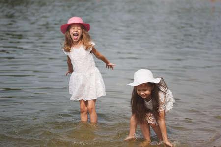 cute happy little girls in sumer lake Stockfoto