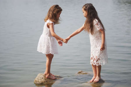 cute happy little girls in sumer lake Stock Photo