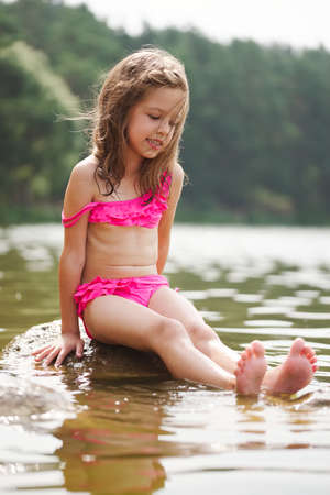 cute happy little girls in sumer lake Banco de Imagens