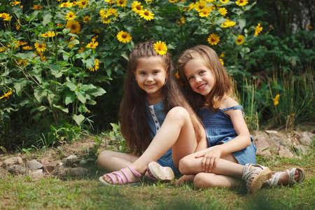 portrait of happy beautiful girls in flowerbed