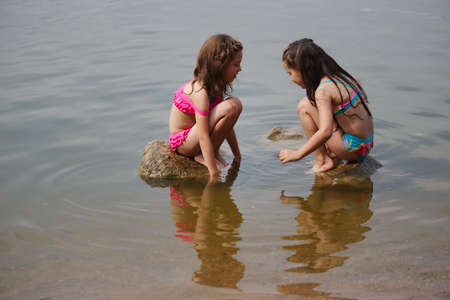 cute happy little girls in sumer lake 写真素材