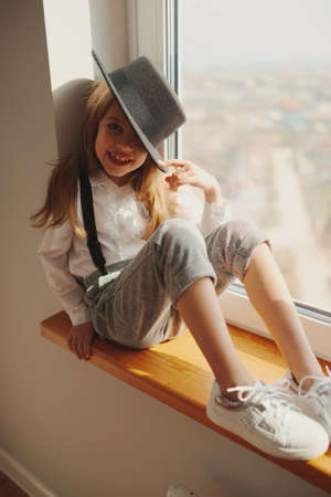 cute little girl with black hat at home Standard-Bild
