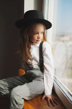 cute little girl with black hat at home 스톡 콘텐츠 - 124400800