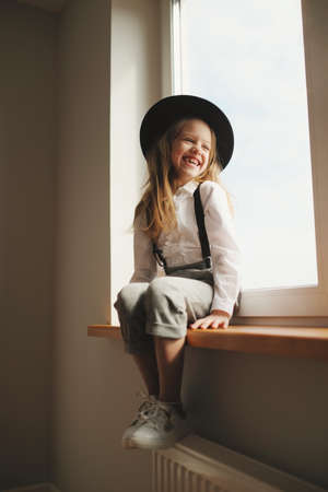 cute little girl with black hat at home 스톡 콘텐츠