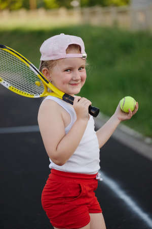 happy girl plays tennis on court outdoors
