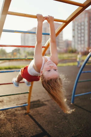 klein meisje heeft plezier op Monkey Bar Stockfoto