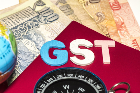 Kuala Lumpur, Malaysia-December 2,2017 : Closeup of GST words with globe, compass and Rupee notes. Selective focus and crop fragment. Editoriali