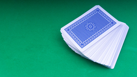 Closeup of playing cards isolated with a green background. Selective focus and crop fragment.