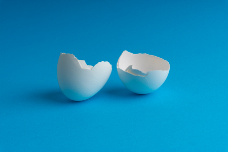 Broken eggshell on the blue background with selective focus Stock fotó