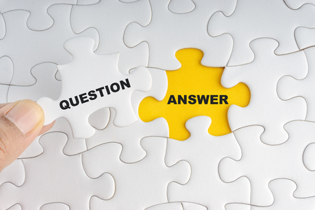 Hand holding piece of jigsaw puzzle with word ANSWER QUESTION. Selective focus Stock Photo